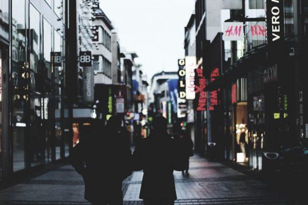 Pessoas na rua passando por lojas
