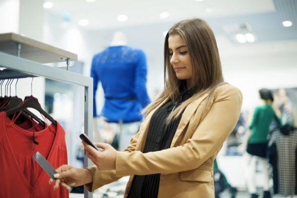 Mulher usando smartphone em lojas de moda