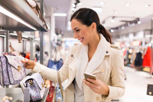 Mulher comprando em loja com smartphone