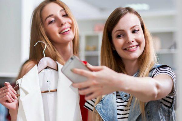 mulheres da geração millennials usando smartphone dentro da loja