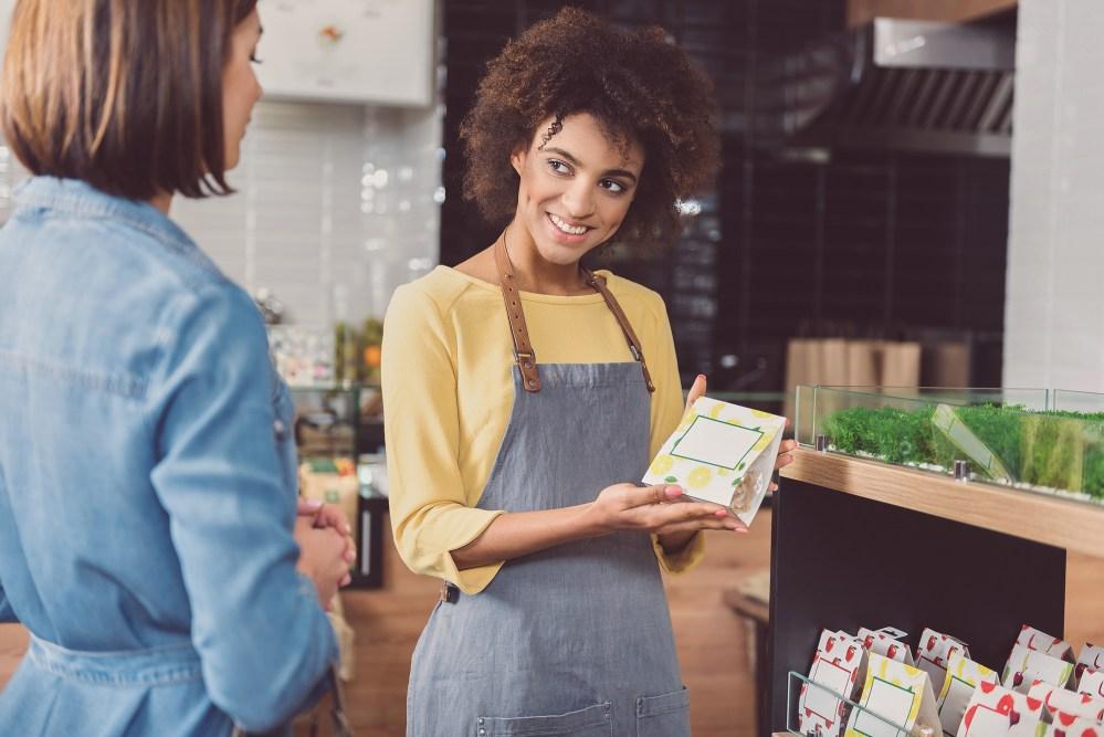 mulher mostrando opções de consumo no PDV